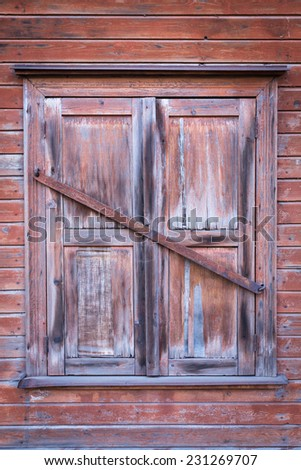 Vintage closed wooden window on old wall - stock photo