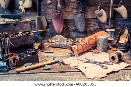 Vintage cobbler workplace with tools, leather and shoes - stock photo