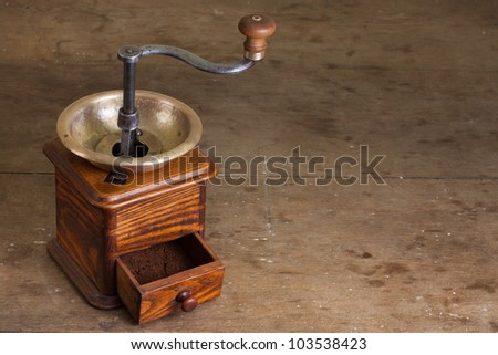 Vintage coffee grinder on old wooden table. Antique, XIX century - stock photo