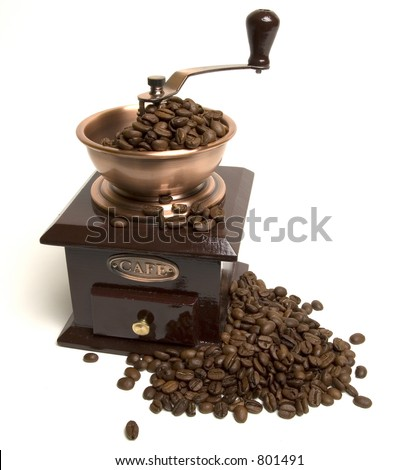 Vintage coffee grinder with coffee beans around it - stock photo