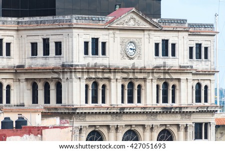 Vintage colonial building with clock, beautiful architectural stone work. Buildings like this can be found all over the tropical island of Cuba. - stock photo