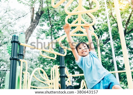 Vintage color tone, Young asian boy hang the yellow bar by his hand to exercise at out door playground under the big tree. - stock photo