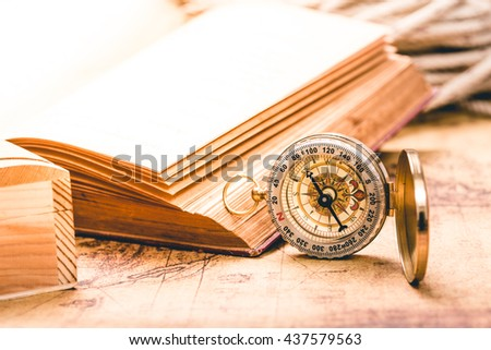 Vintage compass and old book on old map - stock photo