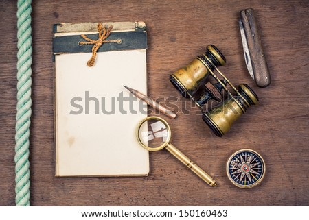 Vintage compass, binoculars, old notepad, pocket knife, pencil, magnifying glass, rope on wooden background - stock photo