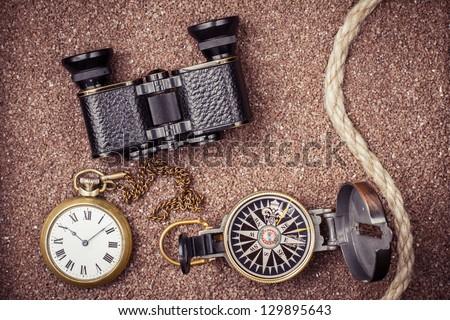 Vintage compass, binoculars, pocket watches on sand background - stock photo