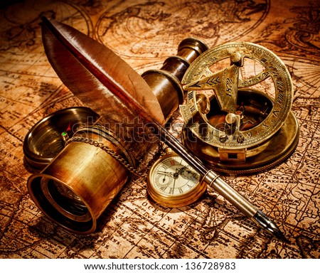 Vintage compass, goose quill pen, spyglass and a pocket watch lying on an old map. - stock photo