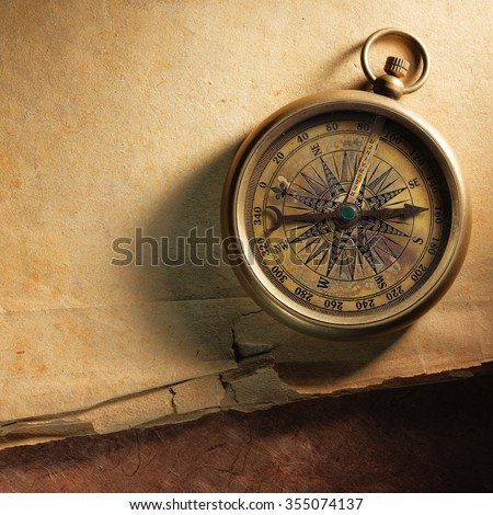 Vintage compass on the very old paper - stock photo