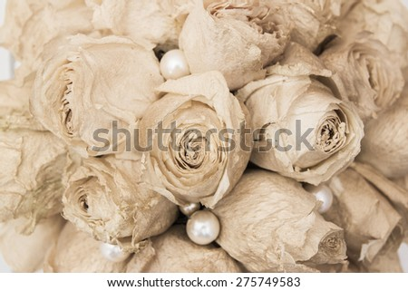 Vintage composition dry bouquet with white roses painted gold and pearl beads. Backdrop useful for wedding cards and other holiday decoration - stock photo