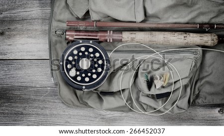 Vintage concept of an antique fly fishing reel and rod with vest and flies on rustic wood. Layout in horizontal format. - stock photo