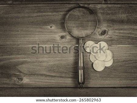 Vintage concept of an antique round shaped magnifying glass and a pile of old silver dollar coins on rustic wood  - stock photo