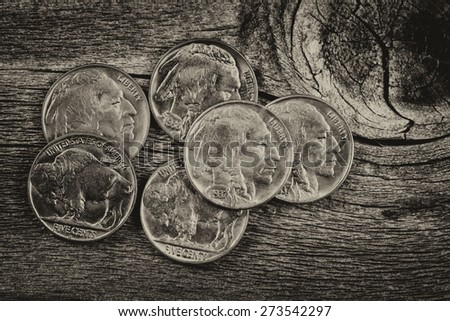 Vintage concept of old nickel coins on rustic wood - stock photo
