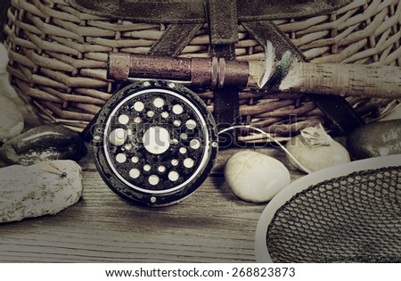 Vintage concept, to include grain effect, of a wet antique fly fishing reel, rod, landing net, artificial flies and rocks in front of creel with rustic wood underneath. Layout in horizontal format.  - stock photo