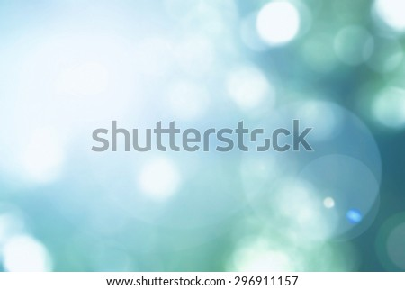 Vintage cool cyan blue green color tone blurred nature background of a view looking up through the foliage of a tree against the sky facing sun flare and bokeh - stock photo