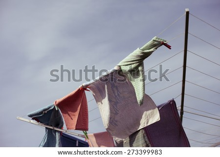 Vintage cotton towels drying on the clothesline on a sunny and windy day - stock photo