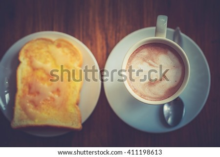 Vintage  Cup of coffee black and brown  on textured wood table hot coffee leaf art , espresso art Hipster   beauty decorate design front of view. Slices of toast bread with butter on wooden table - stock photo