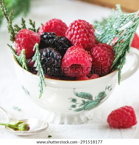 Vintage cup of raspberries and blackberries served with thuja branches and old book on the table. Square image with selective focus - stock photo