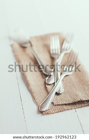 Vintage cutlery, antique silverware, four forks with rough brown cloth on an white painted wooden background - stock photo