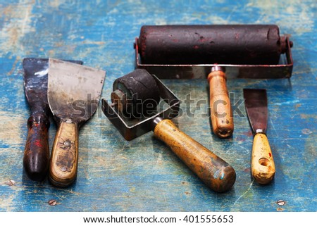 Vintage design artist tools: black rubber roller, big and small putty knives on blue paint wooden background. Diy tools, decorator accessories concept. soft focus, up view - stock photo