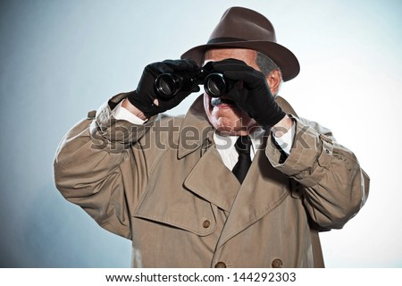 Vintage detective with mustache and hat. Looking through binoculars. Studio shot. - stock photo