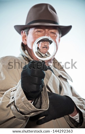 Vintage detective with mustache and hat. Looking through magnifying glass. Studio shot. - stock photo