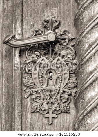Vintage doorknob on antique door, background. Impressive Doorknob with a cross from the medieval city of Bamberg in Bavaria, Germany / Europe, Unesco world culture heritage - stock photo