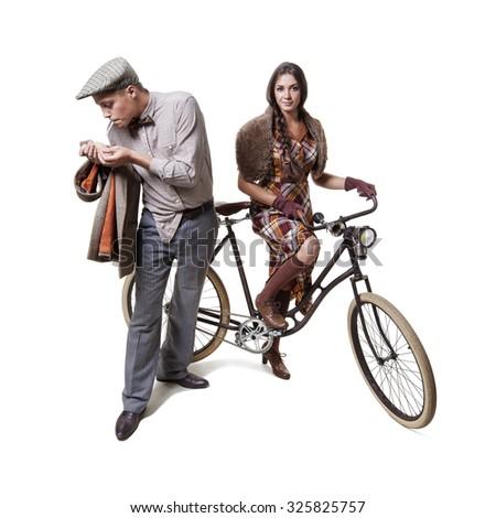 Vintage dressed couple sitting on retro bike - stock photo