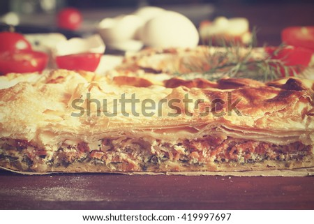 Vintage efekt. Fresh home baking . Pie with fish or vegetables homemade. Cut, side view. eggs, cherry tomatoes, wheat flour, cheese, top view, closeup. Ingredients for baking. - stock photo