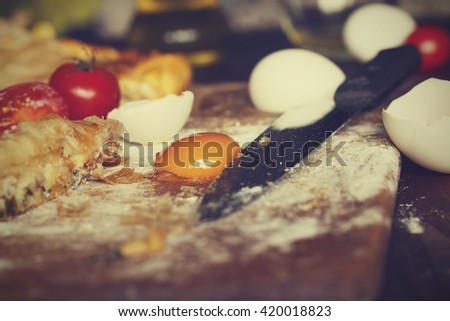 Vintage efekt. Fresh home baking . Pie with fish or vegetables homemade.  eggs, cherry tomatoes, wheat flour, cheese, top view, closeup. Ingredients for baking. - stock photo