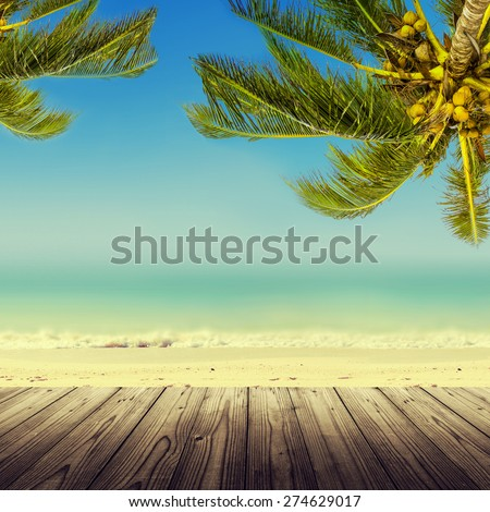 Vintage effect (retro style). Empty wooden table, coconut palm tree, ocean and sandy beach. Tropic island background. - stock photo