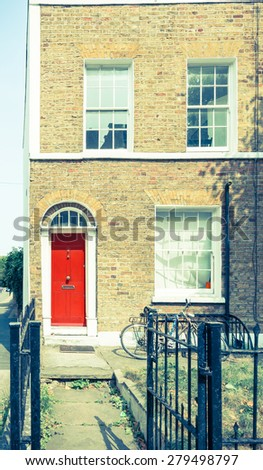 Vintage effect, split East London terrace home with red door. - stock photo