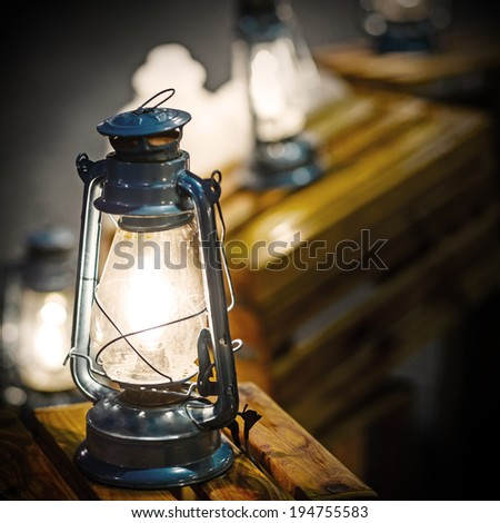 Vintage fashioned rustic kerosene oil lantern lamp burning with a soft glow light in an antique country barn - stock photo