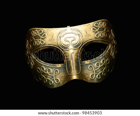 Vintage festive gold dress mask with swirls pattern isolated on black background - stock photo
