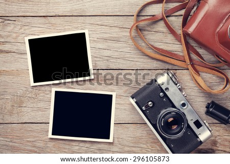 Vintage film camera and two blank photo frames on wooden table. Top view - stock photo