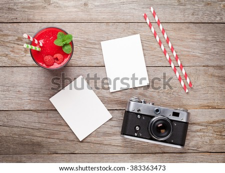 Vintage film camera, two blank photo frames and raspberry smoothie on wooden table. Top view - stock photo
