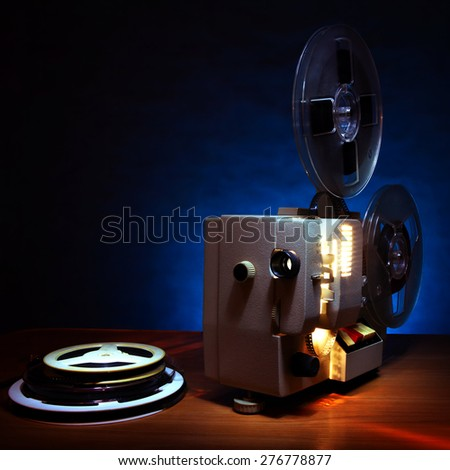 Vintage Film Projector in the Dusk on the Table - stock photo