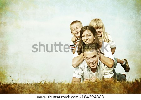 Vintage filtered image of a family lying on green summer grass meadow having happy life - stock photo