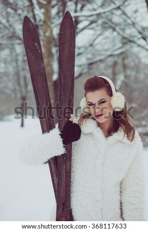 Vintage, filtered image of young woman, posing with wooden ski outdoor - stock photo