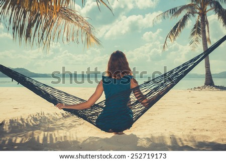 Vintage filtered shot of a young woman sitting in a hammock on a tropical beach - stock photo