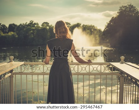Vintage filtered shot of an elegant young woman standing by a lake in a park at sunset - stock photo