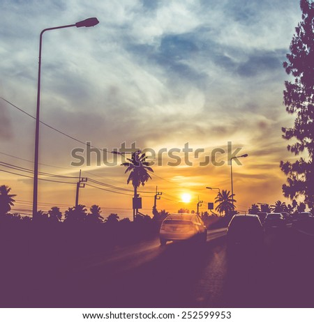 Vintage filtered : silhouette landscape of cars on road,sunset scene in Thailand - stock photo