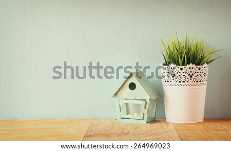 vintage Flower pot and lantern as a bird house against mint wall and antique lace fabric - stock photo