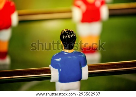 Vintage Foosball, Blue and Red Team Players in Table Soccer or Football Kicker Game, Selective Focus, Retro Tone Effect, Jersey Back as Copy Space - stock photo