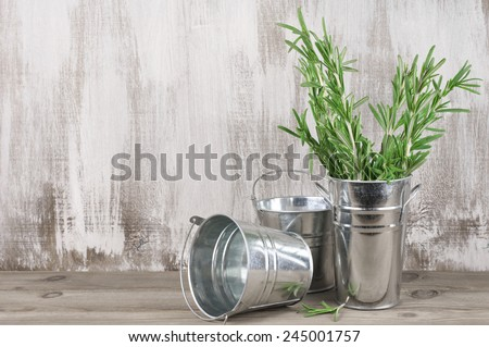 Vintage galvanized buckets with rosemary bunch on rustic wooden background with copy space. - stock photo