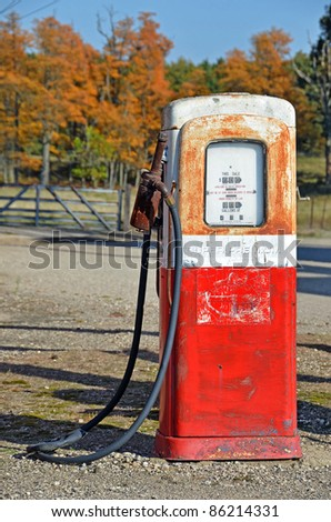 vintage gasoline pump with autumn foliage - stock photo