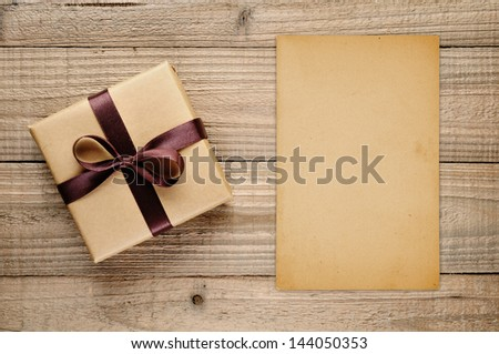 Vintage gift box and blank card on wooden background - stock photo