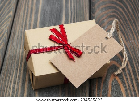 vintage gift box package with blank  tag on old wooden background - stock photo