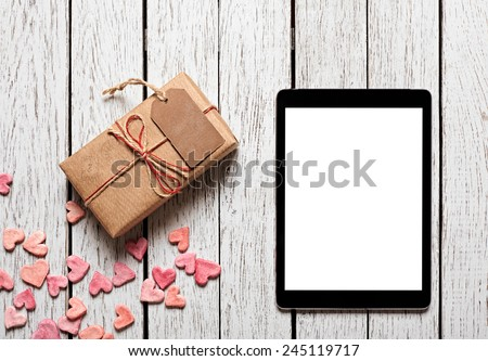 Vintage gift box with gift tag, heap of small hearts and digital tablet computer on white wooden background. - stock photo