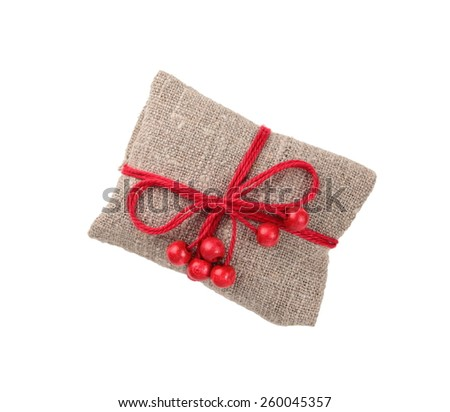 vintage gift in sacking with wooden red beads, isolated on white - stock photo