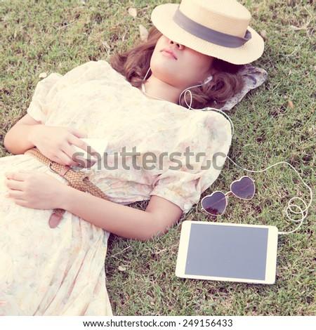 Vintage Girl sleep in park listen music via small talk - stock photo