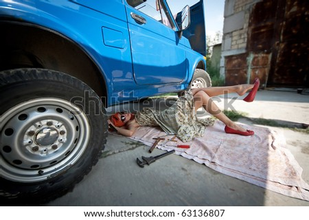 Vintage girl with tools under blue car - stock photo